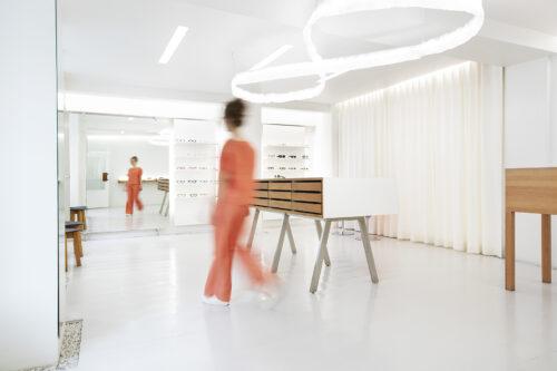 nainen kävelee oransseissa vaatteissa salme optikkoliikkeessä.