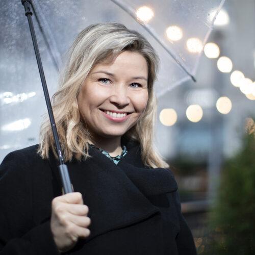 nainen hymyilee sateenvarjon alla.